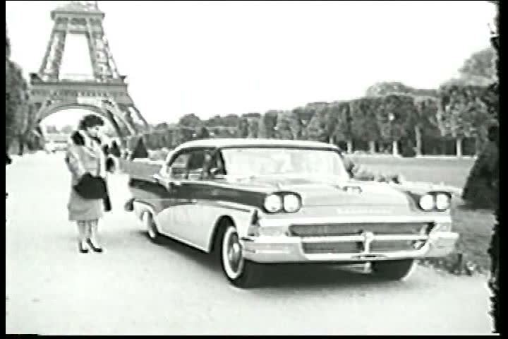 1950s: Paris landmarks are shown before two women, modeling the last Paris fashions, ooh and ahh over the new Ford parked by the Eiffel Tower in 1958.