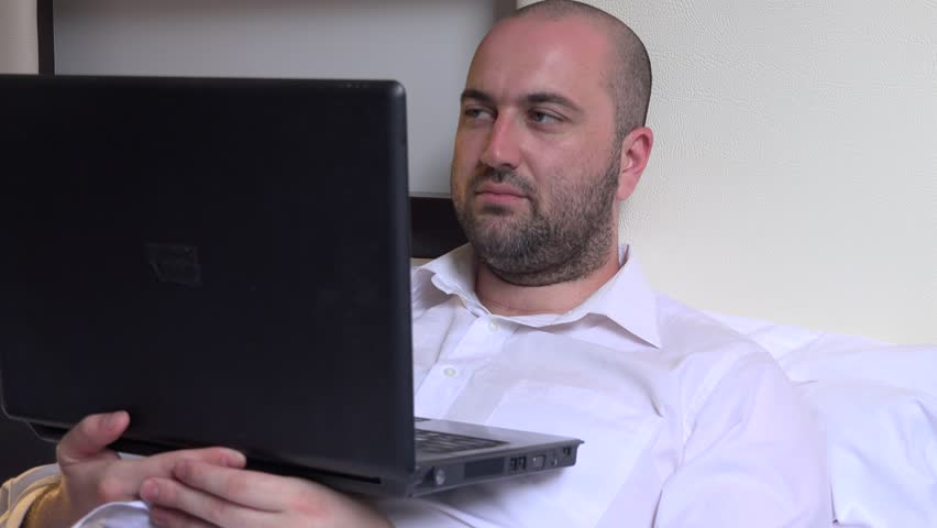 Close up handsome businessman in hotel room watching laptop movie eyes rolling | Shutterstock HD Video #26696668