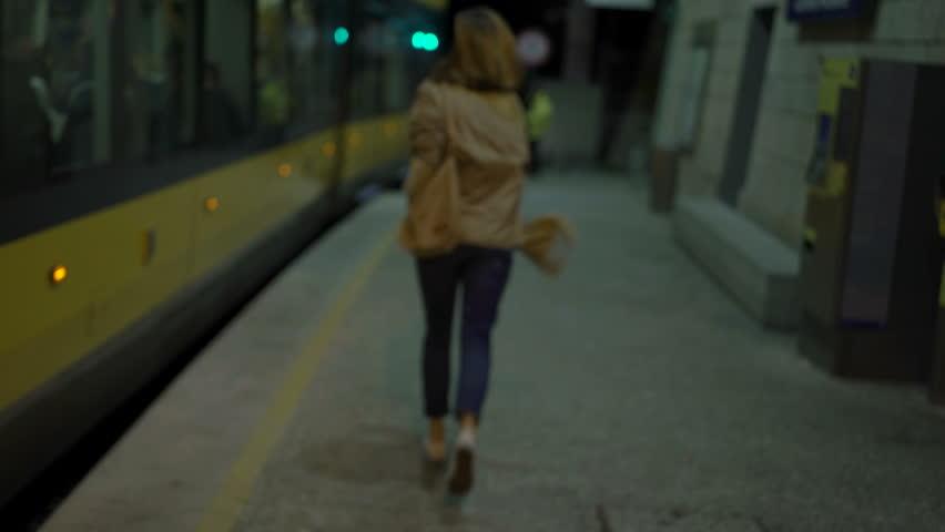 Late, upset woman chasing metro at night