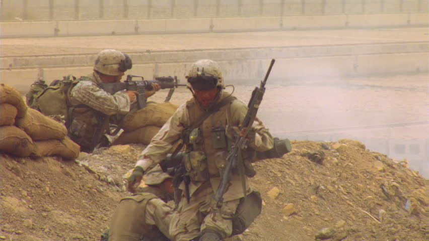 Marines advancing over Iraqi terrain, firing automatic weapons