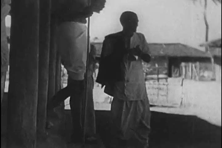 1930s: Mahatma Gandhi leads the Dandi Salt March to protest the taxation of the British Raj and, at the sea, distilling salt with peasant protestors, he is arrested, in 1930.