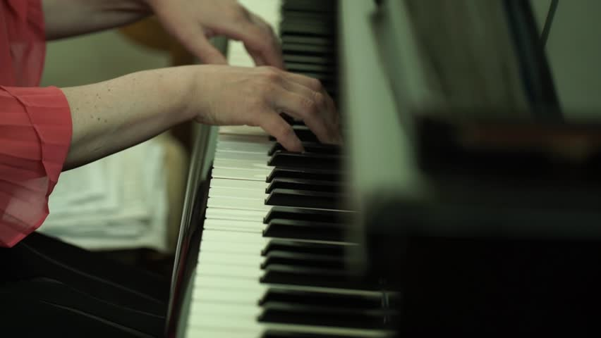 Girl's hands on the keyboard of the piano. The girl plays piano,close up piano. Hands on the white keys of the Piano Playing a Melody. Women's Hands on the keyboard, Playing the Notes Melody.   Shutterstock HD Video #26714131
