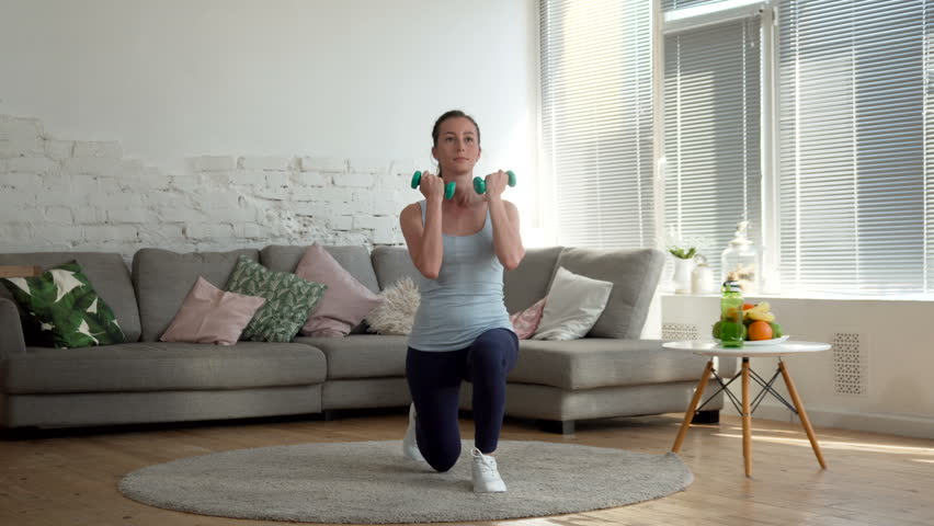 young fit and energetic woman doing sport workout and fitness lunge exercises with weights for healthy lifestyle in living room at home during sunny day #26714371