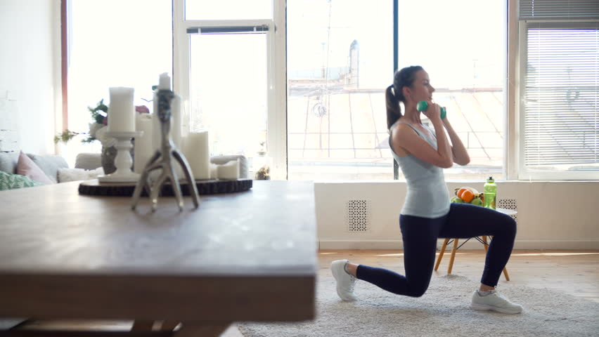 young fit and energetic woman doing sport workout and fitness lunge exercises with weights for healthy lifestyle in living room at home during sunny day #26714386