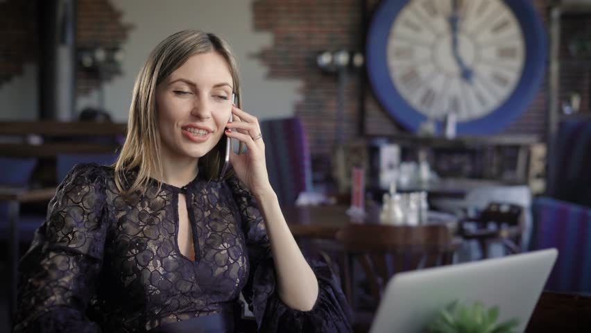 A pretty businesswoman talking to her mobile phone partner, a young woman arranges a meeting in a cozy cafe, where she now sits on a wooden table on which stands a laptop for work Royalty-Free Stock Footage #26715175
