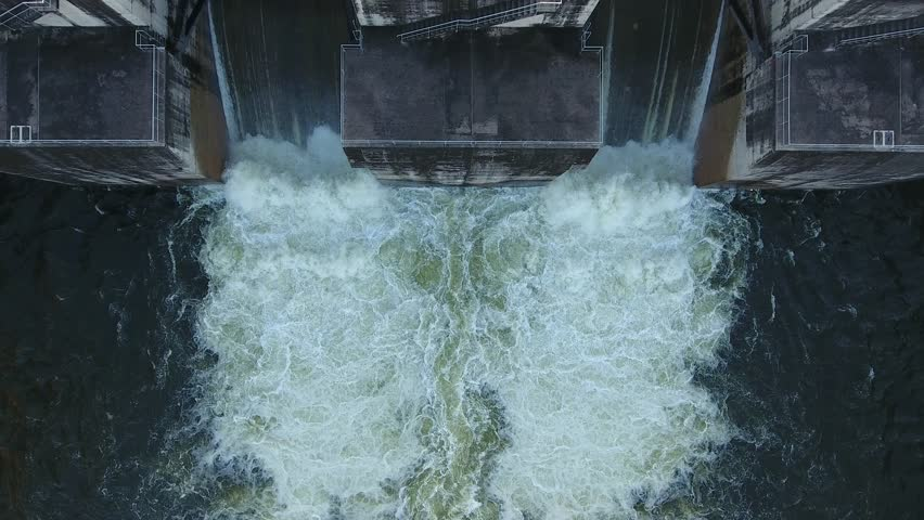 Aerial view of water rushing through the gates at a dam.