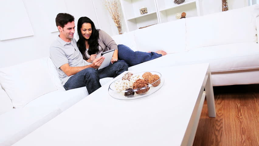 Young heterosexual Latin American couple relaxing home sofa wireless tablet