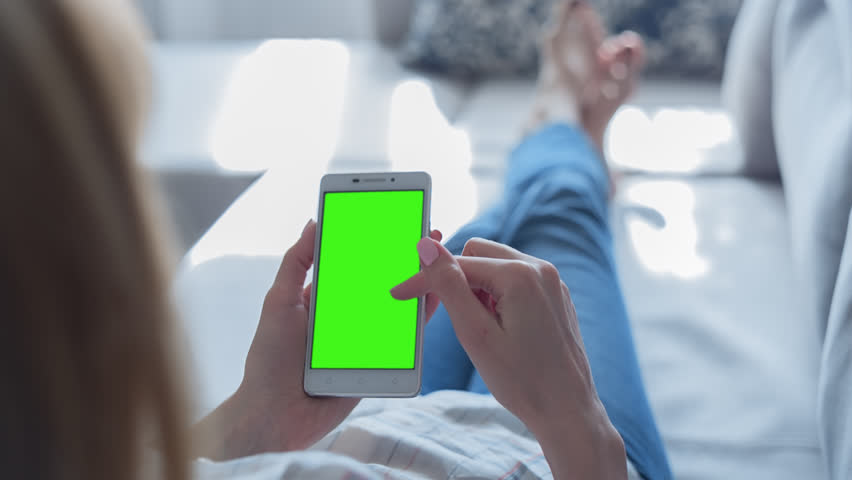 Young Woman laying on a couch uses SmartPhone with pre-keyed green screen. Few types of motion - scrolling up and down, tapping, zoom in and out. Perfect for screen compositing. Made from 14bit RAW | Shutterstock HD Video #26729263
