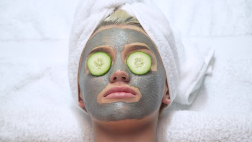 Attractive young blonde model wearing face mask with cucumber on her eyes and towel on her head   Shutterstock HD Video #26738629