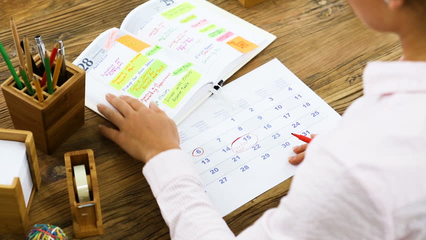 Businesswoman Marking A Date On Calendar After Looking The Schedule From Diary On Office Desk