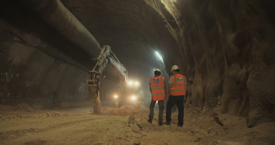 Construction workers supervising heavy machinery during tunnel construction work   Shutterstock HD Video #26747422