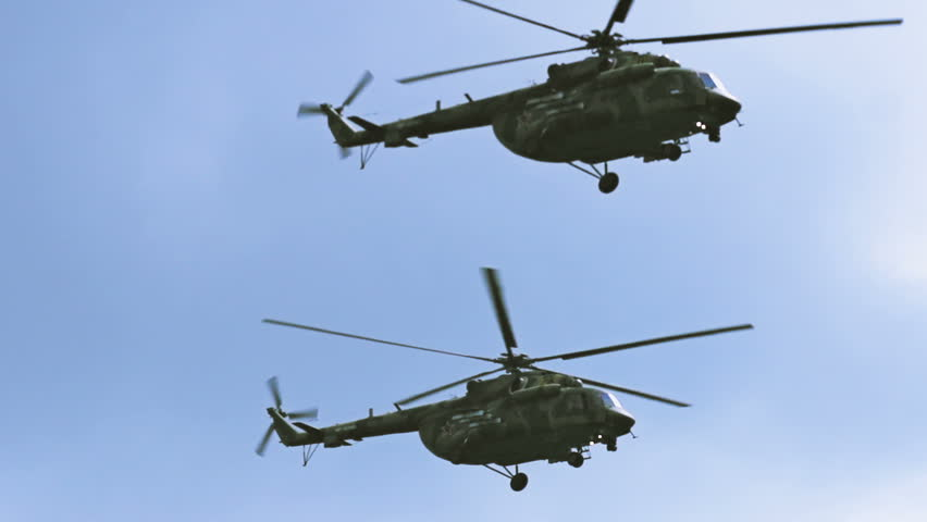 A group of military helicopters flying very close slowmotion. Russian and US Army. Two helicopters fly in slow motion.