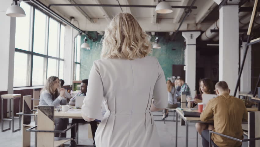 Beautiful blonde female team leader walks through the office, controls the work of employees, gives direction to colleague. #26767045