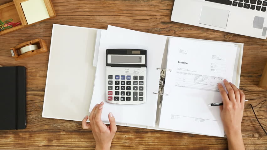 Elevated View Of A Businesswoman Calculating Invoice Using Calculator On Office Desk Royalty-Free Stock Footage #26779252