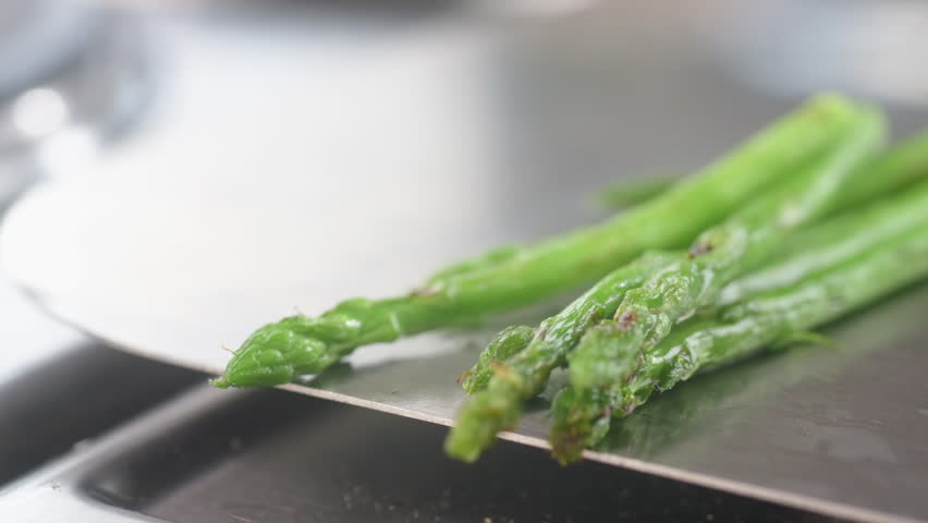 roasted asparagus falls on metal surface slow mo close-up