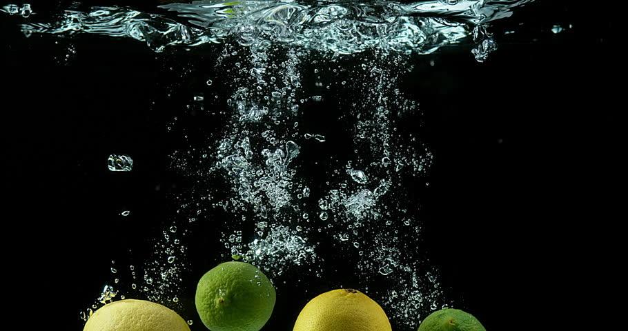 Yellow and Green Lemons, citrus limonum, Citrus aurantifolia, Fruits falling into Water against Black Background, Slow Motion 4K