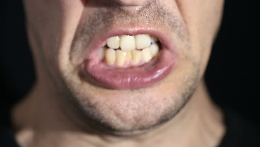 Man screams into the camera on a black background. Mouth and grin close-up | Shutterstock HD Video #26803117