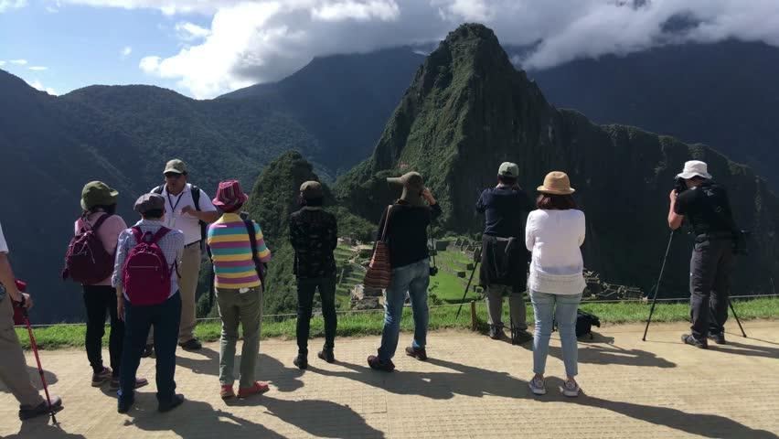 MACHU PICCHU, PERU - APR 10, 2017: Tourists at Machu Picchu, the lost city of the Andes, It is located above the Sacred Valley northwest of Cuzco, Machupicchu District, Urubamba, Cusco Region, Peru.