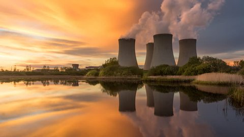 Nuclear power plant by sunset in the landscape with small lake. Timelapse video.
