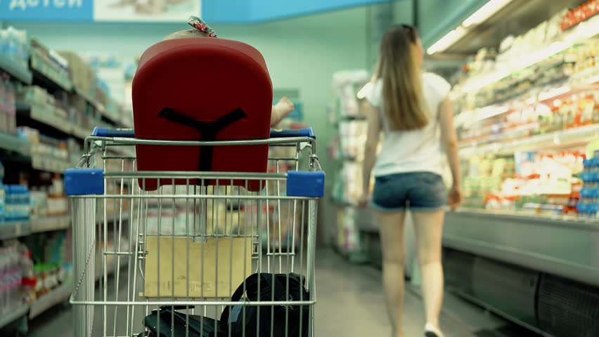 The child sits in a specially equipped chair in the supermarket, his mother chooses the goods, standing at the counter.  | Shutterstock HD Video #26812918