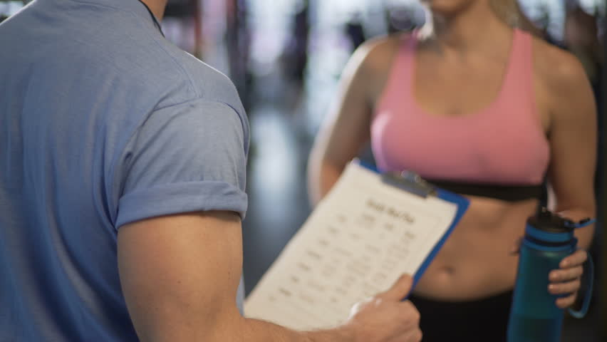 Personal trainer teaching client how to count calories, discussing meal plan. Gym coach talking about nutrition balance with fitness woman, sport club service. Fat food, proteins, body weight program  Royalty-Free Stock Footage #26813347