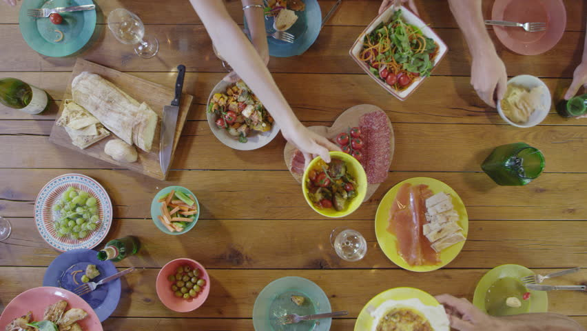 Friends passing food around a dinner table, overhead, shot on R3D | Shutterstock HD Video #26815993