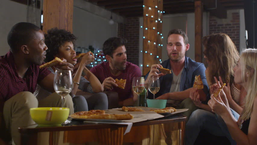 Young adults sharing pizzas at a party at home, shot on R3D #26816065