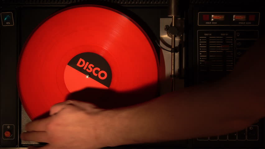 Vinyl record on the player. Plays a song from an old turntable 4k top view. Black background. The music round plate rotate. Music disc turn. Obsolete technology. Hands take a red plate.