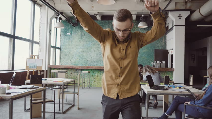 Handsome young businessman doing victory dance about successful achievement. Happy male at modern trendy office.