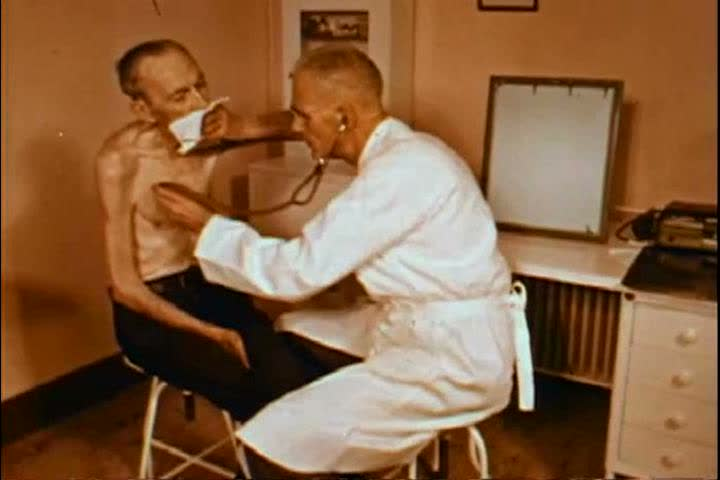 1950s: An emaciated man with emphysema is examined by a doctor in a hospital examination room in the 1950s.