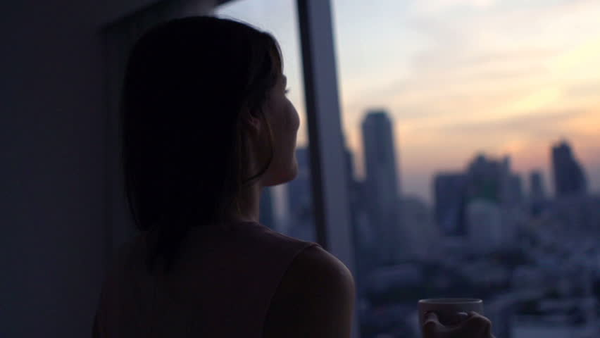 Happy woman drinking coffee and admire view during sunset by window  #26838772
