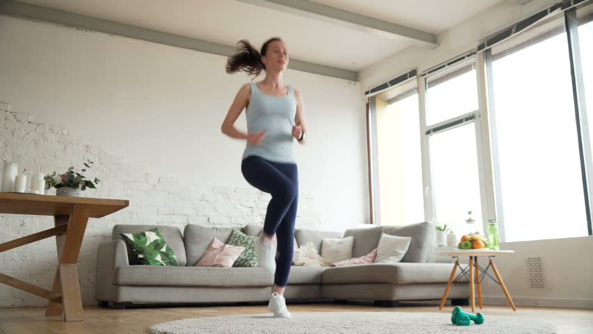 young fit woman warm up running on the spot using app on smart watch to check heartbeat before sport work out for healthy lifestyle at home during sunny day #26856535