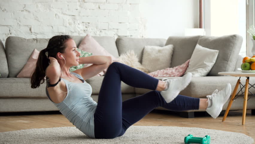 young fit and tone up woman doing fitness workout and sit ups exercises for health using app on mobile phone fixed on hand to listen music in living room at home during sunny day #26856547