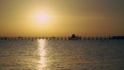 Sunrise in the sea, people are walking along the pier video UHD
