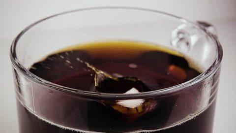 Slow mo. Refined sugar cube falls into a transparent mug with tea