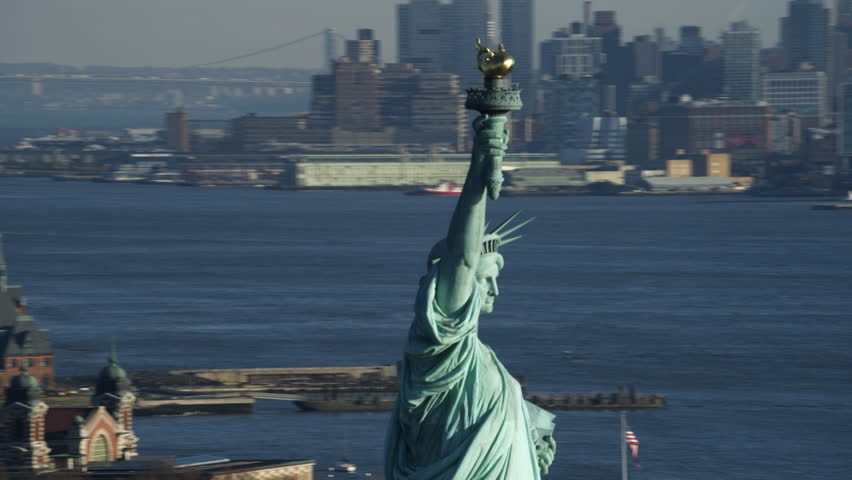 Close orbit of the upper portion of the Statue of Liberty, Jersey City in background. Shot in 2011.