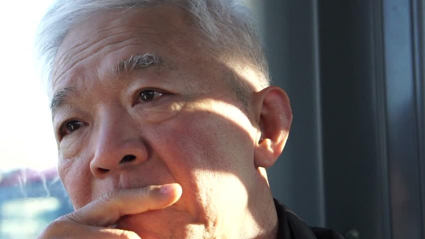 Asian senior elder man thinking in tram while morning sun hitting his face