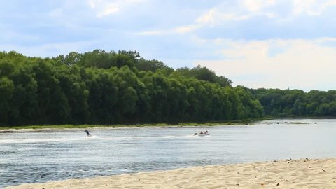 Water sport. Silhouettes of unrecognizable people in motor boat and man waterskiing. Fun on summer river. Active healthy lifestyle concept.  Real time full hd video footage.