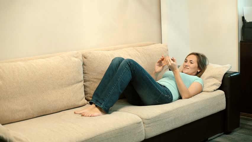 Woman in T-shirt and jeans lying on sofa watching video on smartphone #26901805