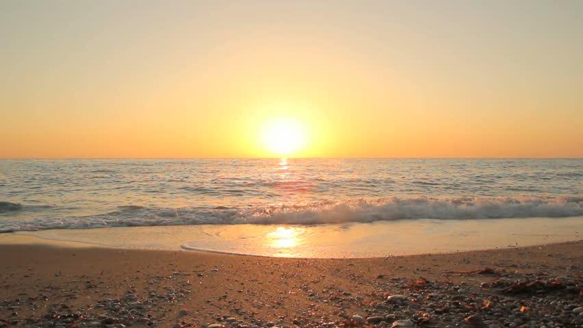 Sunset on the beach - Tranquil idyllic scene of a golden sunset over the sea, waves slowly splashing on the sand