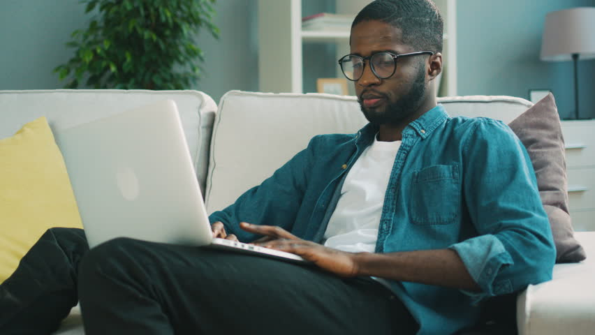 Attractive african American man in glasses sitting on the sofa using laptop at home living background for chatting with friends. Indoor. Technology,job, work Distant learning, lifestyle Online surfing