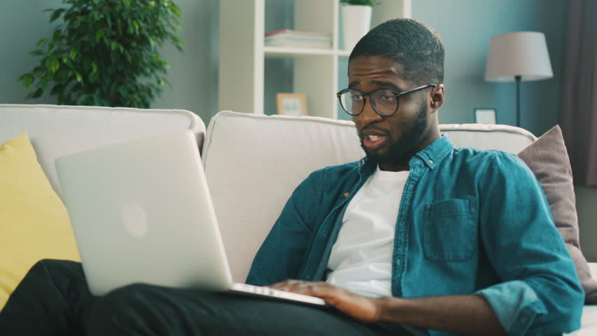 Handsome african man in glasses sitting on couch using laptop for video chatting with friend on living background. Indoor.Pandemic, coronavirus, epidemic, virus, disease, protection, sickness  Royalty-Free Stock Footage #26912560