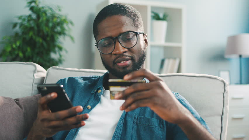 Young african man sitting on the couch, using smart phone for online shopping with credit card on living backround. Indoor.