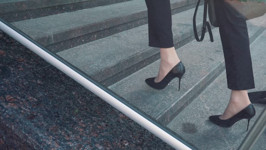 Lower part of business woman in formal suit walking up the outdoor stair.