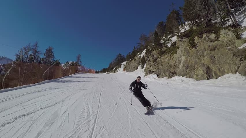 On a Sunny winter's day, a skier in a black suit rolls a carving ski on the ski slope in the mountains, it is removed on the action camera