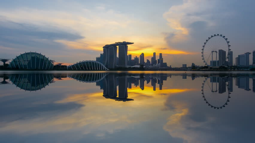 Beautiful Time lapse of Day to Night of Singapore skyline with reflection. 4K UHD. Zoom Out Camera Motion.