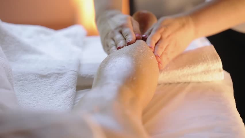 Young woman having feet massage in beauty spa salon, close up. Masseur kneads the foot and leg of a young beautiful girl at candle background