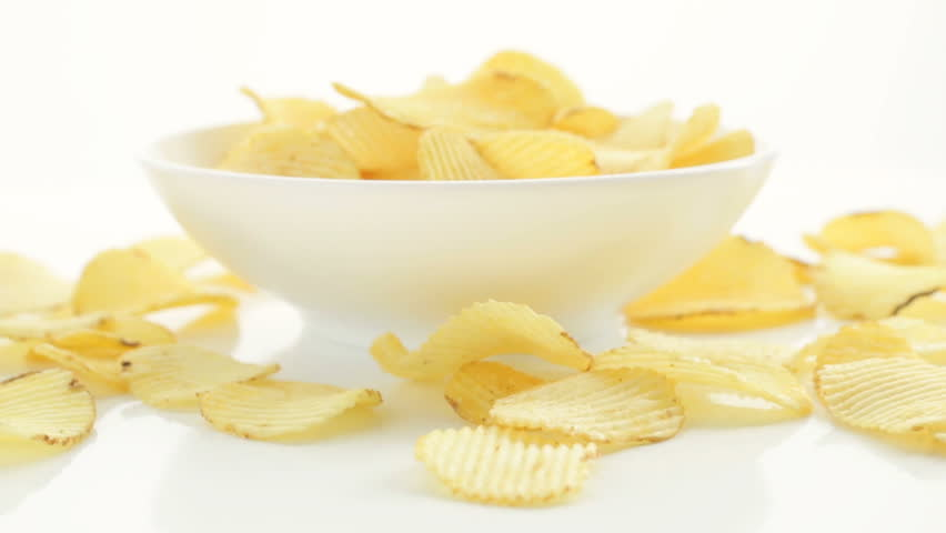Unhealthy Harmful food, yellow delicious Potato ribbed crispy chips randomly lying in bowl and on a white table background, close-up footage movement forward | Shutterstock HD Video #26931685