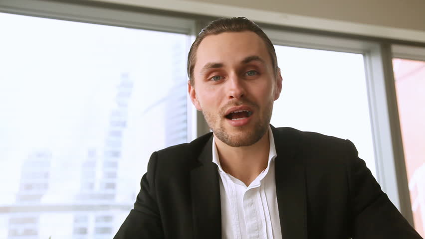 Young cheerful businessman offering services for business, looking at camera, talking, making video call, participating in online conference, presenting statistical report showing company stock growth   Shutterstock HD Video #26933878