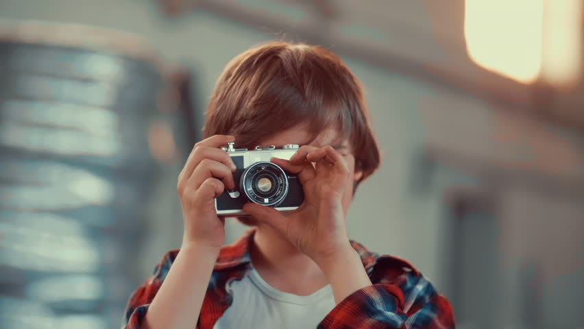 boy taking photo with an old film camera. shot in slow motion #26938165
